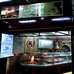 שלט שמציע בשר עגל וצלעות כבש בבית קפה חמודי שבסמטאות השוק בעכו
